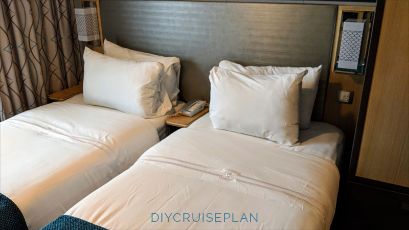 Two twin beds with crisp white linens on a cruise ship