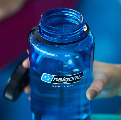 Person holding a blue-green Nalgene 1 liter bottle with open lid
